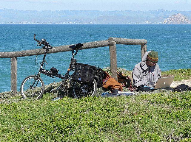 man on laptop in outdoor wilderness